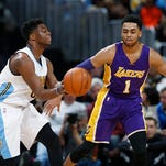 Denver Nuggets guard Emmanuel Mudiay, left, passes the ball as Los Angeles Lakers guard D'Angelo Russell defends in the first half of an NBA basketball game Wednesday, March 2, 2016, in Denver. (AP Photo/David Zalubowski)