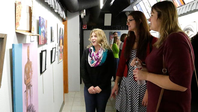 From left, Liz Budelman, Claudia Tryon and Sarah Razner enjoy an art piece at Share Fine Arts Gallery in Fond du Lac.