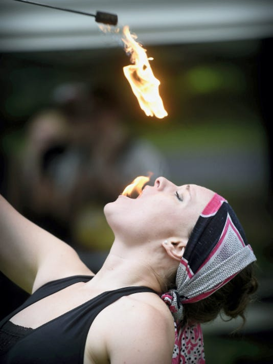 Kelsey Lee, Philadelphia, puts out her fire the hard way, by swallowing the flames. The South Sixth Street Playground became a stage for the flow arts as dancers moved to music and spun hoops — and other props — lit afire.