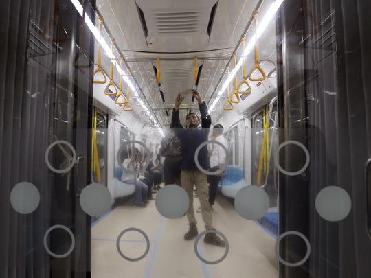 In this Feb. 21, 2019, photo, a man takes a selfie inside Mass Rapid Transit (MRT) during a trial run in Jakarta, Indonesia.