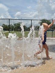 Amelia D'Albora, 3, enjoys running through the fountains