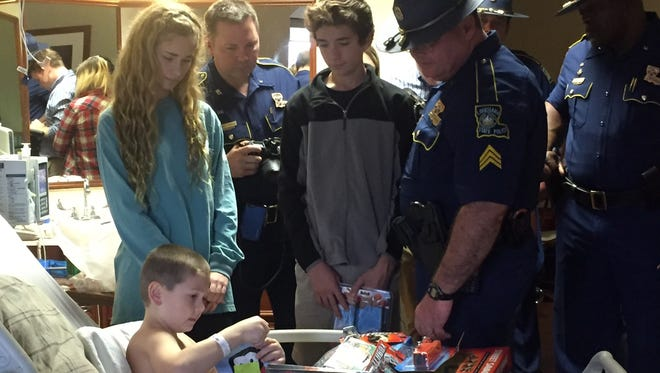 Hunter Rogers, 6, opens a gift he received Thursday at Rapides Regional Medical Center's Women's and Children's Hospital. Troopers from Louisiana State Police Troop E and their family members delivered gifts to children at hospitals throughout the region on Christmas Eve.