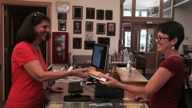 Peggy Ashcraft, left, a volunteer at the Ulysses Philomathic Library, assists patron Louise Kahn at the circulation desk.