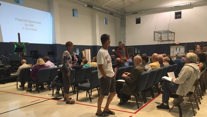 Community members file into their seats Wednesday at the Salem Church of Darmstadt for a public meeting regarding the upcoming judicial review.