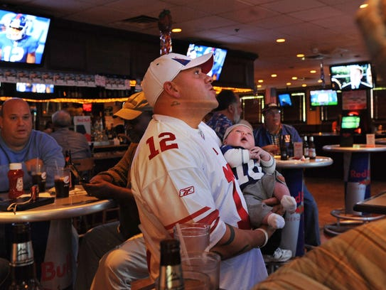 Logan Rossi and his seven-week old, son Dominic Laido, L-R, watched the game at Redd's Bar & Restaurant in Carlstadt.