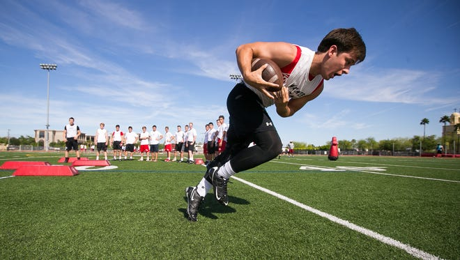 Brophy College Prep's Walker Adams picks up the ball during a drill at their boys high school football practice in Phoenix on Thursday, April 30, 2015.