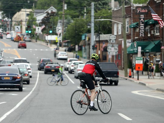 Bicyclists cross Route 119 in Elmsford to get to the South County Trailway bike path May 28, 2018.