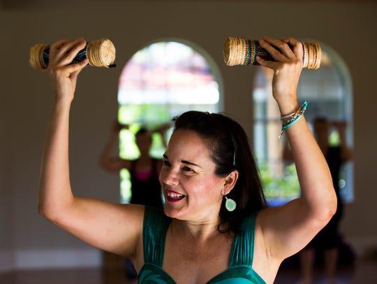 Instructor Winnie Purple uses shakers during a Hawaiian-inspired