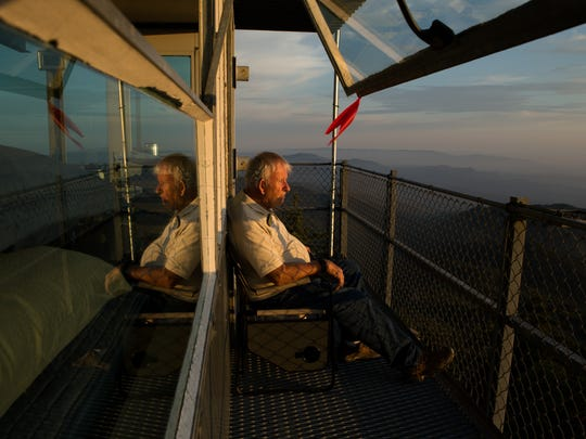 Black Mountain Fire Lookout volunteer Richard Hart watches the sunset at the end of his shift on June 23, 2017.