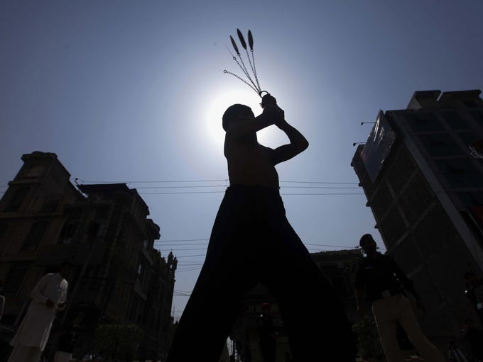 A Pakistani Shiite Muslim boy is silhouetted against