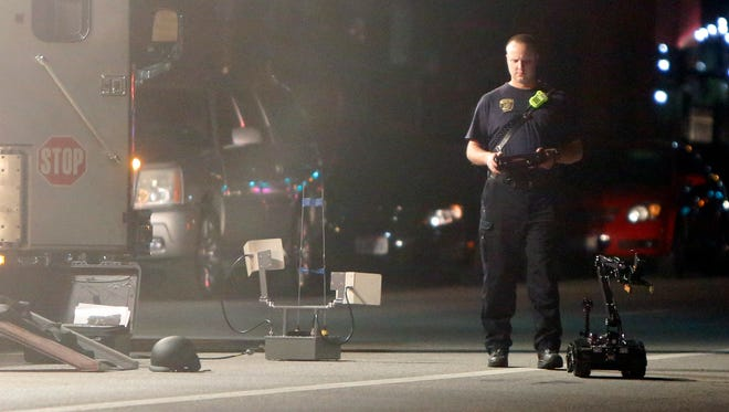 The bomb squad investigates a suspicious object on Central Parkway Monday night. The object was determined to be a beer keg.