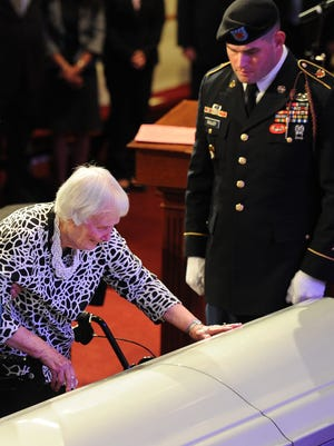 Helen Cooke touches the casket of her late husband Pfc. Cecil E. Harris of Shelbyville, Tenn., as her son Eddie Harris looks on. A World War II soldier, Harris was killed in action in France in 1945 but his remains were not discovered until last year.