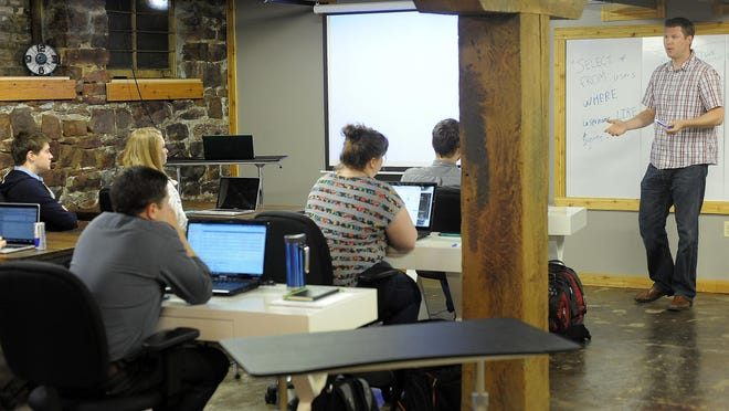 Josh Stroschein (right) instructs during Code Bootcamp, an eight-week course in web development, in the Rock Island Building in downtown Sioux Falls on Wed., June 17, 2015.