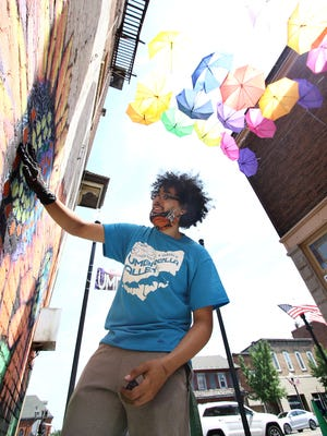 Alliance-based artist Andrew Wells rubs chalk on to the brick walls of Umbrella Alley just off Louisville's Main Street as he and other artists create large sunflowers as part of a large block-long mural during an event Saturday.