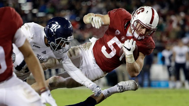 Stanford running back Christian McCaffrey (5) leaps into the end zone on a 23-yard touchdown reception during the first half of an NCAA college football game against Rice, in Stanford, Calif. McCaffrey will skip his senior season to enter the NFL draft. McCaffrey announced his decision on Wednesday, Dec. 7, 2016, saying he has done everything he could in college and playing in the NFL has been his dream since childhood. (AP Photo/Marcio Jose Sanchez, File)