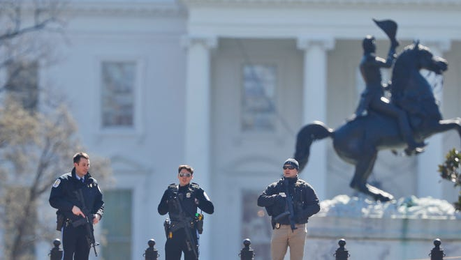 Law enforcement officers stand at the entrance to Lafayette Park across from the White House in Washington, after they area was closed to pedestrian traffic on March 3, 2018. A man apparently shot himself along the north fence of the White House midday, according to the Secret Service.
