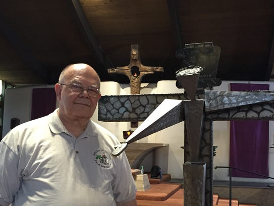 Father John Kavcak stands next to a  special cross