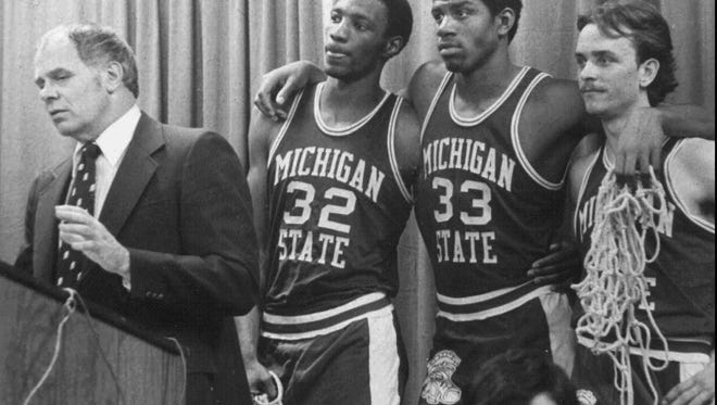 """FILE-Michigan State players Greg Kelser, left, Earvin """"Magic"""" Johnson, center, and Terry Donnely listen to Michigan State coach Jud Heathcote during a news conference, in this MSU file photo. Heathcote's coaching career ended when the Spartans lost to Weber State 79-72 in the NCAA Southeast Regional tournament, Friday, March 17, 1995, in Tallahassee, Fla. Heathcote's 24-year coaching career, 19 at Michigan State, ended with a record of 340-220 at Michigan State and 420-273 overall, and one NCAA title in 1979. (AP Photo/Michigan State, file)___DT7"""