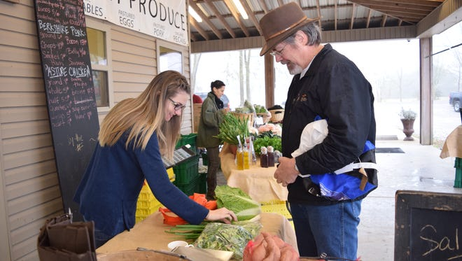 Carmen Buswell rings up produce for Robert Zoehfeld at the Inglewood Farm Saturday market. Inglewood Farm uses the Louisiana Grown logo on its website and farmers market displays.