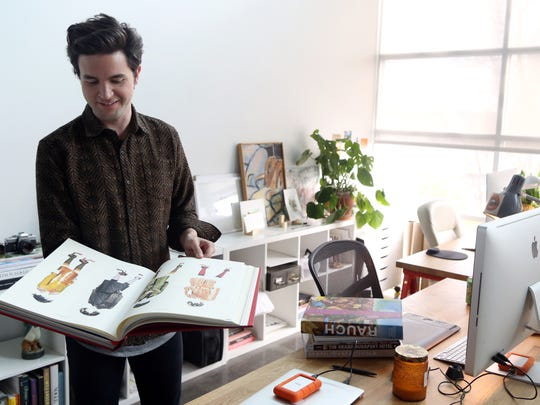 Brett Warren flips through a fashion book he keeps in his office at the co-working space WELD Thursday March 23, 2017.