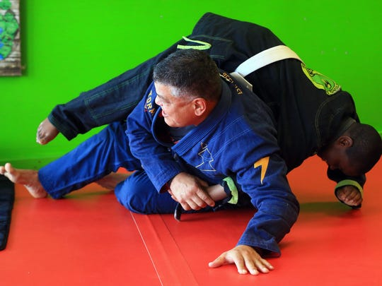 John Barrera shows Frank Allen techniques during practice Thursday, April 13, 2017, at Strong Arm Mixed Martial Arts in Corpus Christi.  Barrera placed first in the regular division and open division of the Pan Jiu-Jitsu International Brazilian Jiu-Jitsu Federation Championship in March.