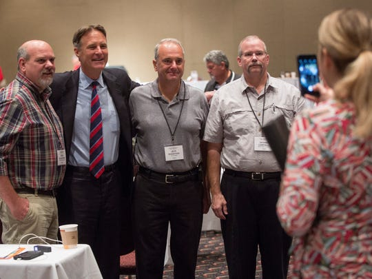 Evan Bayh, center left, poses for a photo with members of the Indiana State Building and Construction Trades Council Tuesday afternoon at the Horizon Convention Center. A new poll released shows Democrat Evan Bayh leading Congressman Todd Young in the U.S. Senate race.