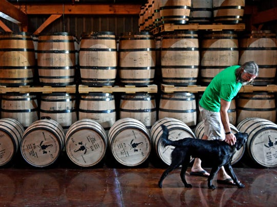 Lee Kennedy and his dog Scout past rows of whiskey aging in barrels at the new Leiper's Fork Distillery.