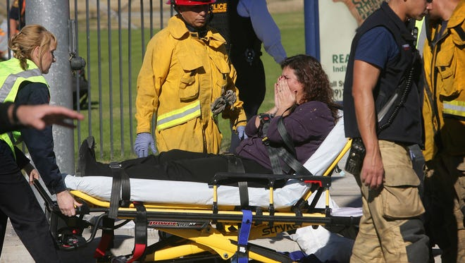 A victim is wheeled away on a stretcher following a shooting that killed 14 people and wounded many others at a social services facility on Dec. 2 in San Bernardino, California.