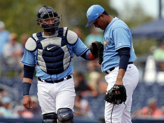 FILE - In this March 7, 2018, file phot, Tampa Bay Rays catcher Jesus Sucre, left, pats pitcher Yonny Chirinos on the chest as Chirinos struggles during the fifth inning of a spring training baseball game against the Baltimore Orioles in Port Charlotte, Fla. The Rays are arming their catchers with quarterback-style wristbands in response to rule changes governing mound visits and the team's plan to shift to a four-man rotation. (AP Photo/Chris O'Meara, File)