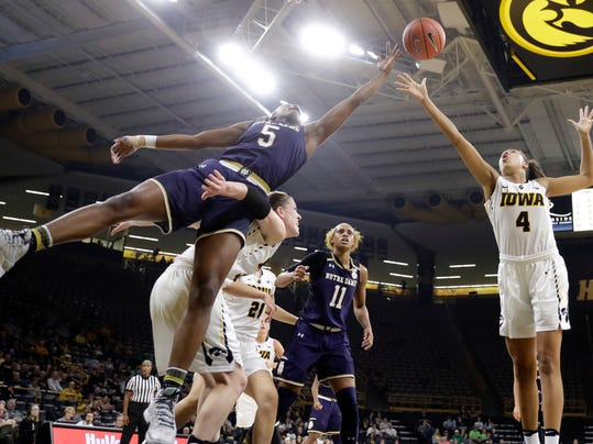 Notre Dame guard Jackie Young (5) fights for a rebound with Iowa's Christina Buttenham and Chase Coley (4) during the first half of an NCAA college basketball game, Wednesday, Nov. 30, 2016, in Iowa City, Iowa. (AP Photo/Charlie Neibergall)