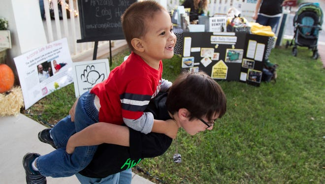 Paul Kettner picks up his brother, safe-haven baby Porter Olson, as the two play Friday during a fundraising and awareness drive for the Arizona Safe Baby Haven Foundation in Glendale. The group aims to raise awareness of Arizona's Baby Safe Haven law.