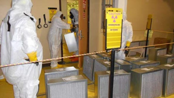 Radiological workers ready sued filters for off-site disposal.