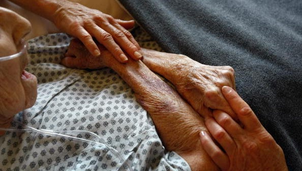 Hospice volunteers caress the hands of a terminally ill patient in Lakewood, Colorado.