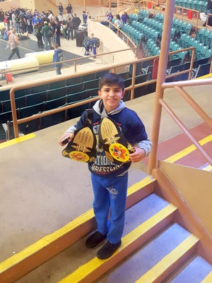 Marcus Najera, 12, stands with his two national championships belt at at Saturday's Greater Southwest Nationals wrestling tournament in Albuquerque.