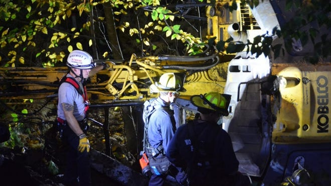 Firefighters at the scene of the accident off Leland Hill Road in Sutton late Tuesday.