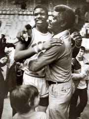 Bosse's Derrick Dowell is hugged by his father (Macon, right) following a game at Roberts Stadium in 1982.