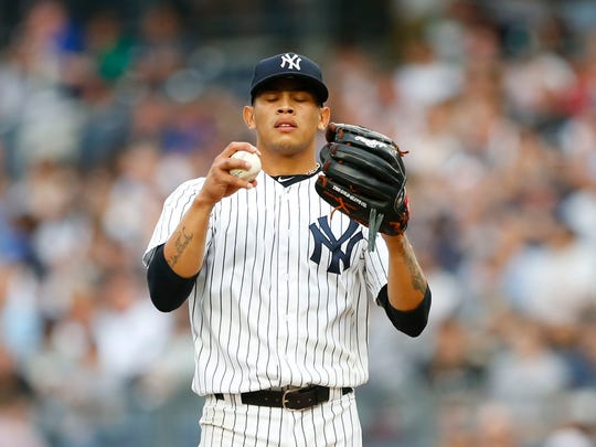 New York Yankees starting pitcher Jonathan Loaisiga (38) pauses before pitching against the Seattle Mariners in the first inning  at Yankee Stadium.