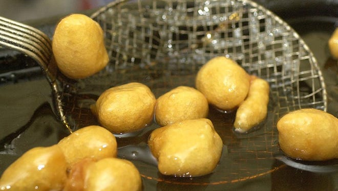 At the Grecian Festival, loukoumades (honey puffs) made from deep-fried dough are scooped out of a warm mixture of honey syrup.