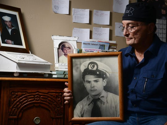 Junny Rios Martinez sits in his home and looks at a photo of his father Abraham who recently passed away. Behind him are photos of his sons Jeremy (in Navy uniform) and Junny.
