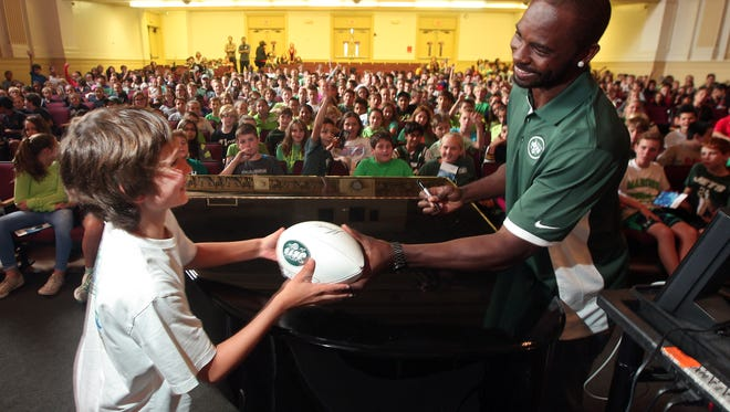New York Jets Jaiquawn Jarrett hands off an autographed football to Harding Twp Scholl sixth grader Grant Meyers after the NFL safety spoke about the importance of physical activity and healthy eating to nearly 400 Morris County students and teachers at Madison Junior School kicking off the Jets PLAY 60 Challenge. September 22, 2015, Madison, NJ.