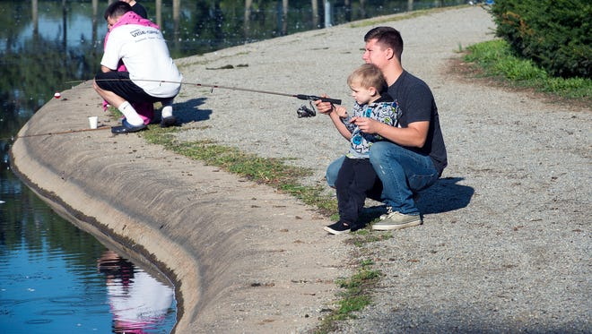 Brandon Smith of Manchester Township, right, helps his son Keegan Shue, age 4, fish during the annual York-Adams County Central Labor Council fishing derby.