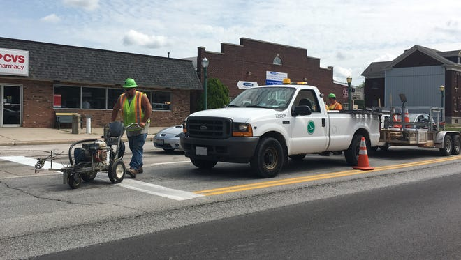 ODOT crews paint lines on U.S. 20 in Woodville on Thursday afternoon.