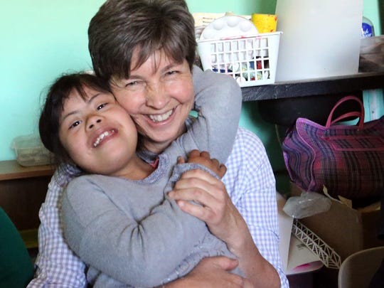 Sister Carol Wirtz gets a hug from Reyna Gonzalez, 8, at the clinic she helped create in the Anapra area of Juarez.