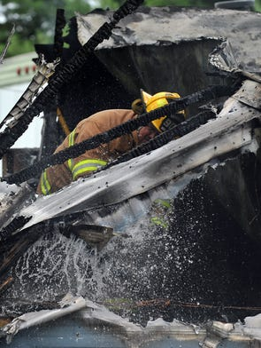 A firefighter sprays down a what's left of a trailer Friday afternoon, Aug. 22, 2014, in Clearcreek Township. Firefighters responded to the call shortly after 1 p.m. near the intersection of US 22 and Ohio 674.
