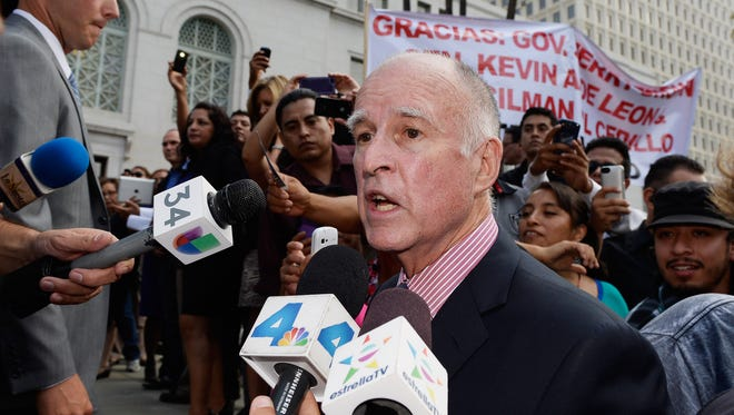 Gov. Jerry Brown speaks after signing AB 60 on the steps of Los Angeles City Hall  on Oct. 3, 2013.
