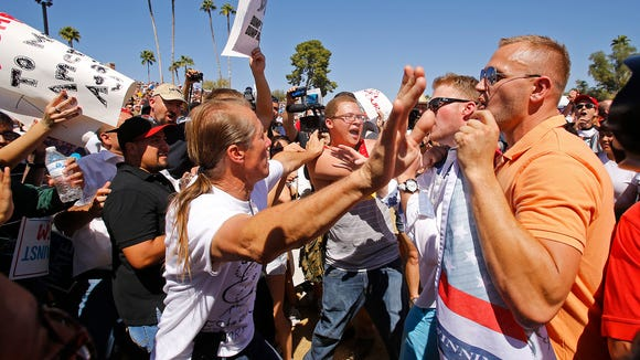 Donald Trump supporters and protesters clash as the  presidential candidate speaks during a rally Saturday, March 19, 2016 in Fountain Hills, Ariz.