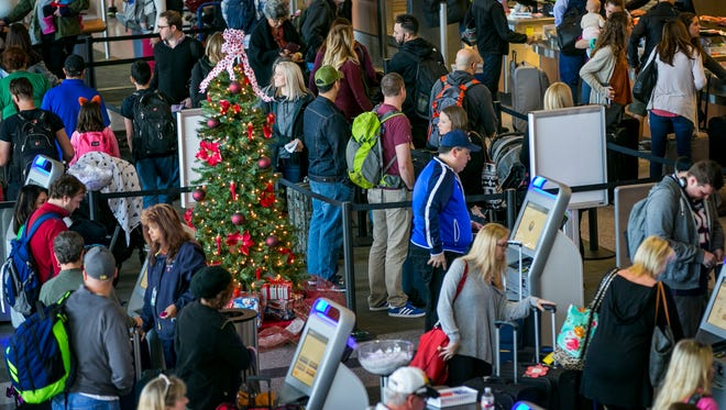 A Christmas tree is surrounded by travelers at the Southwest Airlines ticket counter on a busy day at Austin-Bergstrom International Airport in Austin, Texas, on Thursday, Dec. 22, 2016.