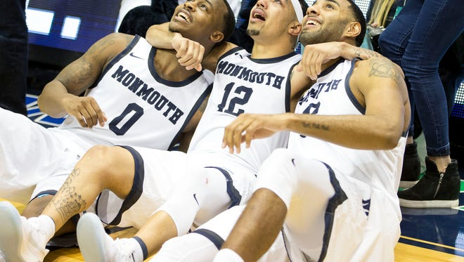 Monmouth's Justin Robinson celebrates after the game for being the top scorer in Monmouth University history.  Robinson celebrates with teammates Josh James and Chris Brady. Saint Peter's at Monmouth University basketball. West Long Branch, NJFriday, February 3, 2017.@dhoodhood