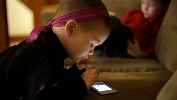 Nolan Young, 3, front, looks at a smart phone while