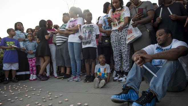 Hubert Latham sits near the candles lit in his son honor during a candlelight vigil for 12-year-old Jajuan Hubert Latham at Danny Mayfield Park on Sunday. Jajuan was fatally shot in a drive-by shooting while sitting in the back seat of his father's vehicle.